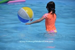 girl playing with beach ball in pool