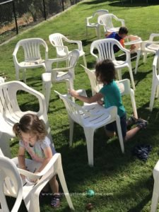 three children cleaning chairs