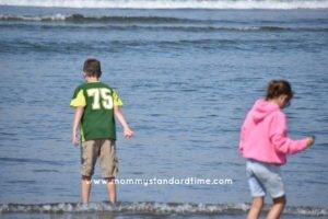 brother and sister wading at coast