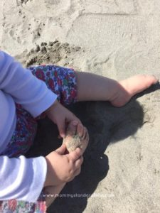 baby feet and hands in sand