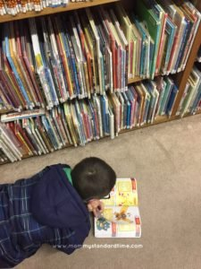 boy reading book at library