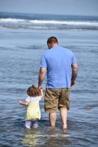 dad and toddler wading at coast