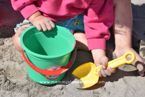 toddler with sand toys