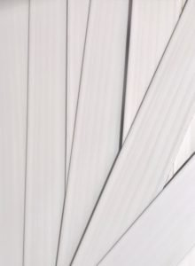Stack of white faux wood window blind slats